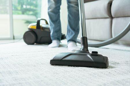 Frauen, die Teppich im Wohnzimmer mit Staubsauger reinigen.