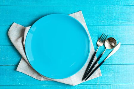 Empty blue ceramic round plate with table cloth,knife,spoon and fork on blue wooden background. Stock Photo
