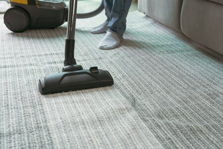 Women using vacuum cleaner cleaning carpet in the living room . Imagens