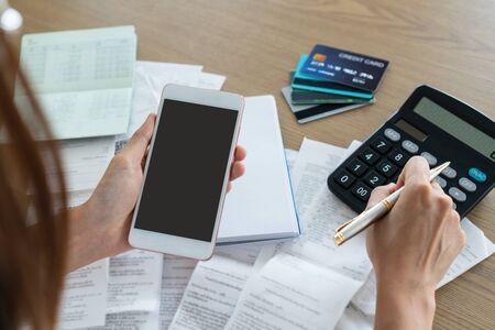 Vrouw die mobiele telefoon vasthoudt en rekenmachine, account en spaarconcept gebruikt.