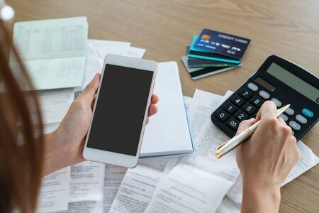 Woman holding mobile phone and using calculator , account and saving concept.