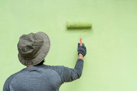 Back view of young men painter in T-shirt and gloves painting a wall with paint roller.