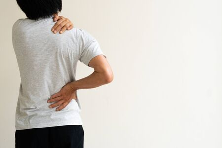 Young man holding his back in pain. Medical concept