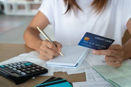 Woman holding credit card and writing, account and saving concept.
