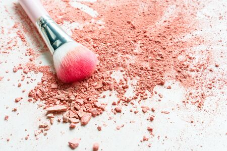 Smear of crushed orange blush on as sample of cosmetics product and brush, copy space, top view 写真素材