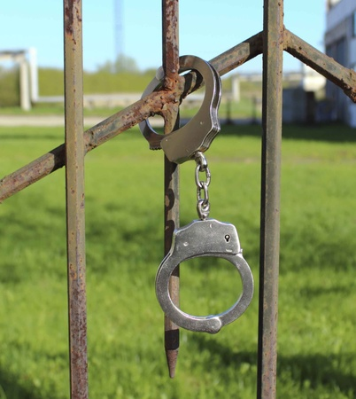 lock in handcuffs to the fence symbolizes captivity Stock Photo - 13418387