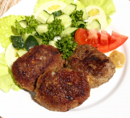 this is a baked turkey cutlets, served with fresh vegetable salad Stock Photo - 14265700
