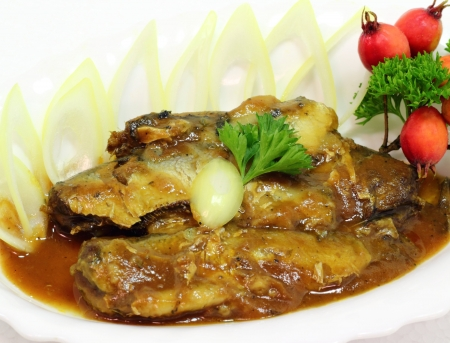 sprats in tomato sauce with onions on a white plate  photo