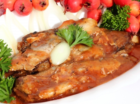 sprat: sprats in tomato sauce with onions on a white plate