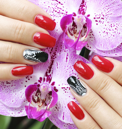Beautifully manicured fingernails with orchid flowers in the background