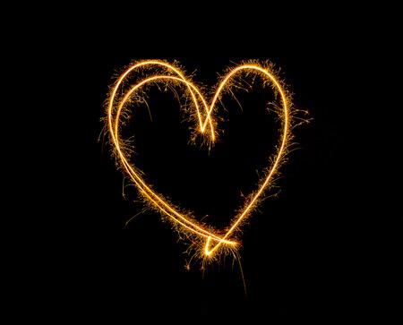 Sparkler firework light alphabet HEART solated on black background.