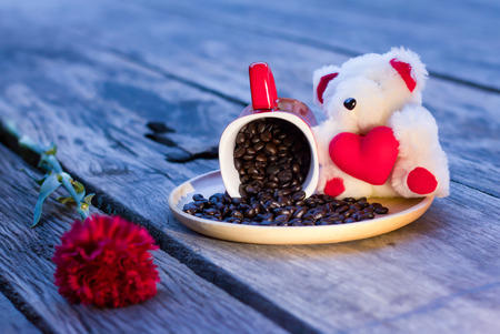 valentine day cup of coffee: Valentine Day background,Teddy Bear holding heart shape and coffee bean in red cup on wood background. Stock Photo