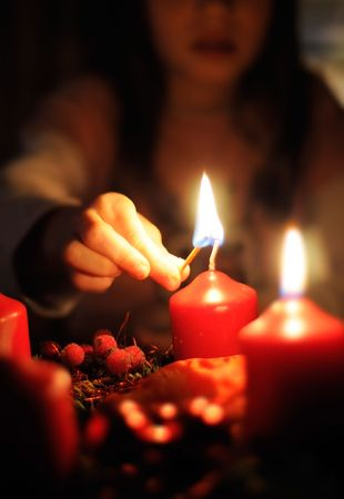advent time: Girl light a Candle on a Christmas Wreath Stock Photo