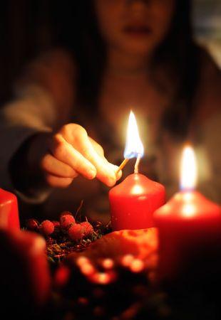 Girl light a Candle on a Christmas Wreath Stock Photo