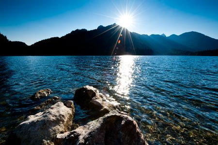 alpine water: Late Sun over Schwarzensee, a Lake in Upper Austria. With Lens Flares Stock Photo