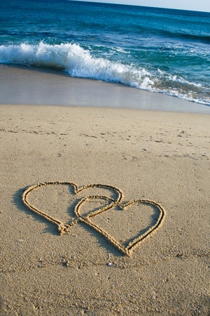 Two ensambled hearts drawn in the sand of a beach Standard-Bild