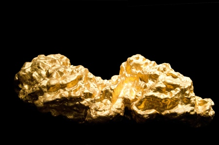 materia prima: Pepitas de oro sobre un fondo negro con profundidad de campo