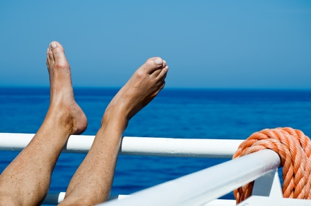 Feet on the railing on a cruise liner