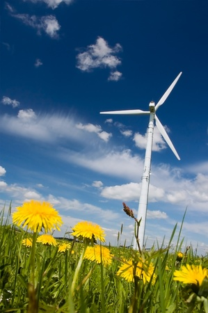Wind Turbine in a spring meadow full with dandelions photo