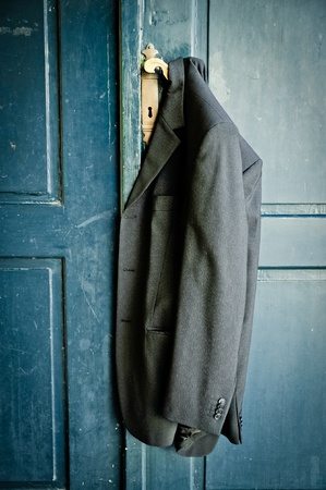 hanging clothes: Mans coat hanging on a handle of a vintage door