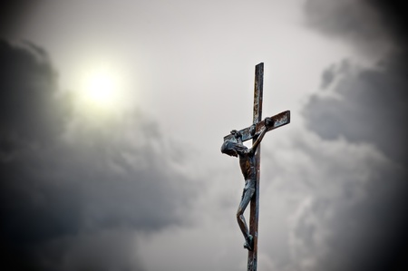 Cross with jeus in front of dark clouds photo