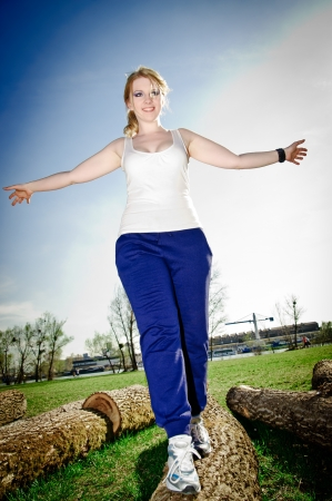 Young woman balance over a tree trunk photo