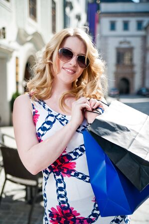 Blonde young woman with shopping bags photo
