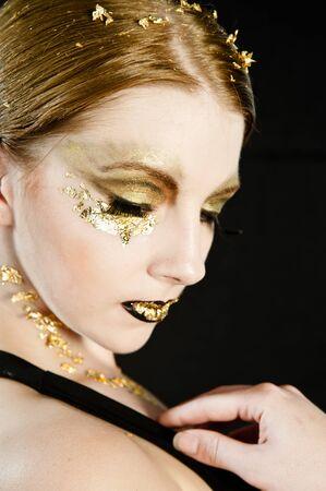 maquillaje de fantasia: Retrato de una mujer rubia de oro en su cara Foto de archivo