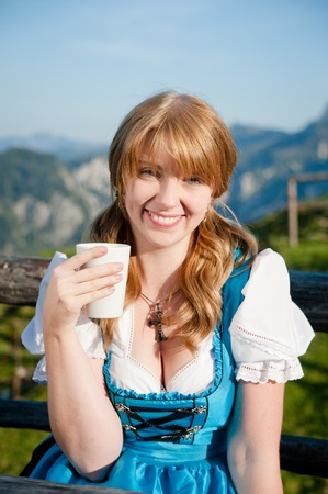 joyful girl in traditional dirndl with cup of milk Stock Photo