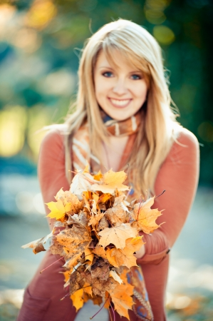 Blonde woman holding a bunch of autumn leaves Stock Photo