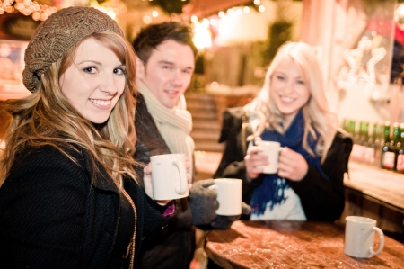 christmas drink: Three Young People drinking Punch at Christmas Market