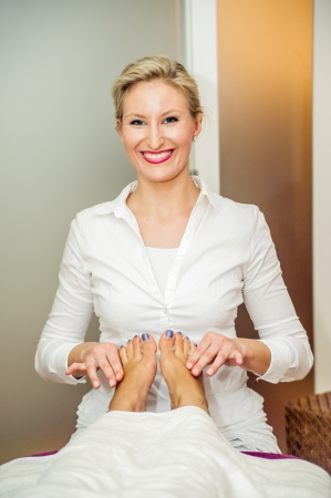 Blonde therapist make a reflexology foot massage photo