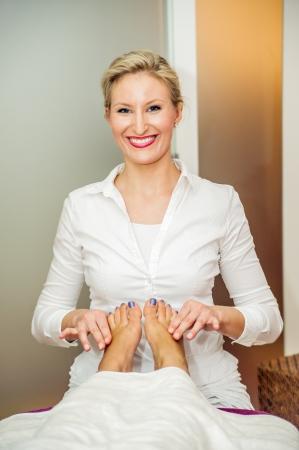 Blonde therapist make a reflexology foot massage