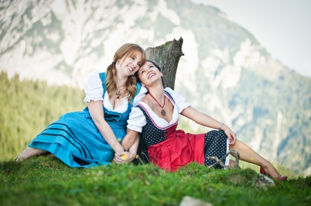 Two cheerful woman dressed in dirndl in the austrian alps photo