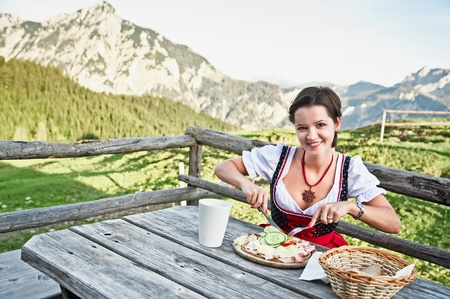 austrian: Young woman in dirndl eating brettljause in the austrian alps