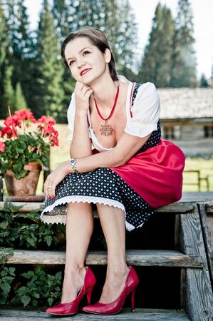 cheeful: Young woman in dirndl Sitting on woode Steps in the alps