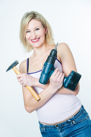 Blonde woman with hammer and screwdriver in her hands photo