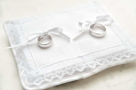 rose ring: White pad with two wedding rings on it Stock Photo