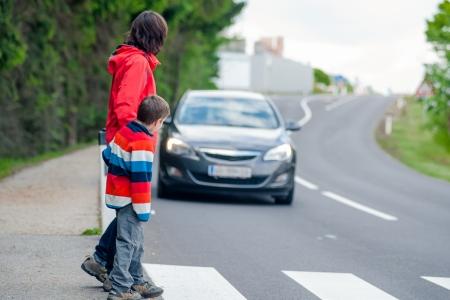 crosswalk: Madre e hijo pasa una calle cuando un coche que ven�a Foto de archivo