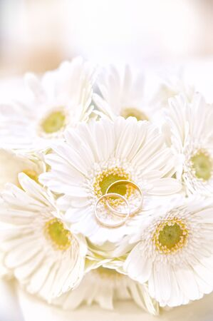 Twi wedding rings on a bouquet of white flowers