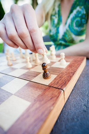 Close up of female hand moves piece in chess photo