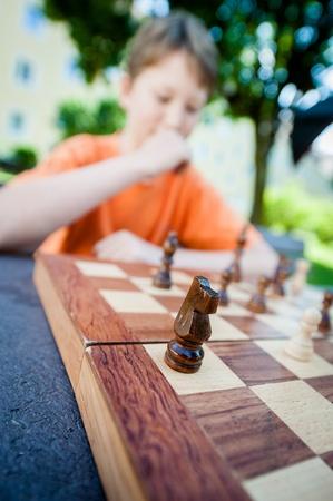 contemplates: Boy contemplates his next move in a game of chess.