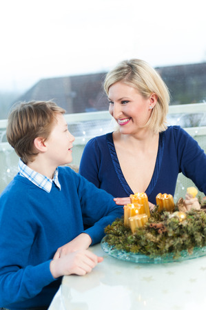 Mother and Son sitting by a Christmas Wreath photo