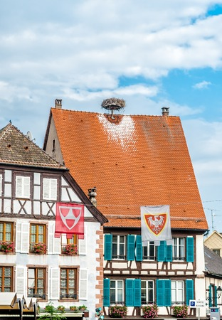 Frame house with storks nest on the roof in Colmar, France