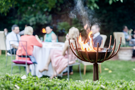 eating in the garden: Group of people enjoying a garden party. In the foreground a Firebowl