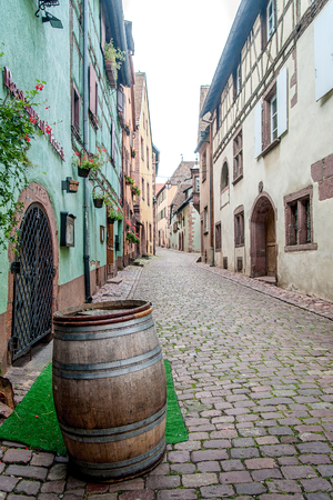 wine road: Old Alley with Wine Barrel taken in Alsace, France Stock Photo