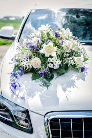 cowl: White wedding car with flower bouquet on the cowl Stock Photo