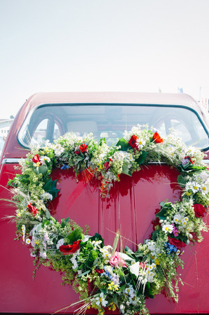Heart shape bouquet on the rear end of a red wedding car