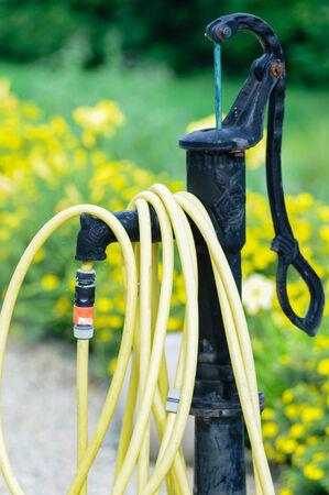 garden fountain: common home garden hose coiled up and hanging on a fountain