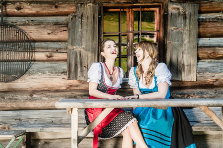 Two cheerful women in traditional austrian outfit photo
